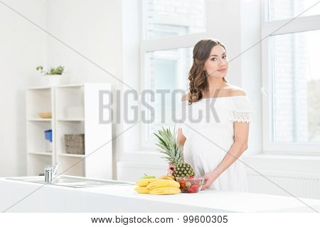 Beautiful pregnant woman washing a pineapple.
