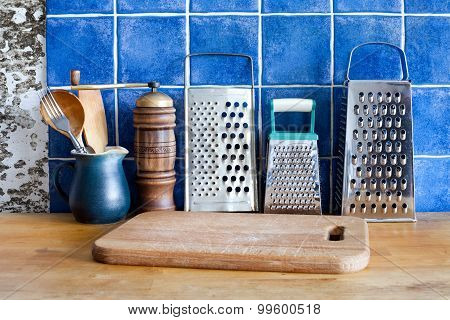 Different Kinds Stainless Steel Grater, Green Jug,  Spoons, Cutting Board.