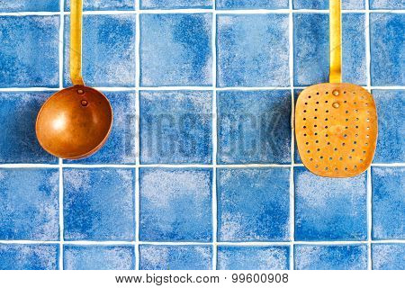 Vintage Copper Spoon And Skimmer Hanging Against Blue Tile Wall.