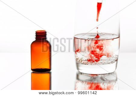 Medicine Dropping Into A Glass Of Water