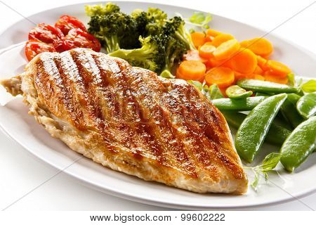 Roast chicken fillet and vegetables on white background