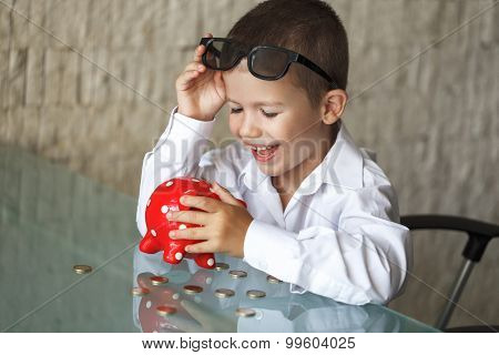 Happy Little Manager Boy With Coins And Piggy Bank