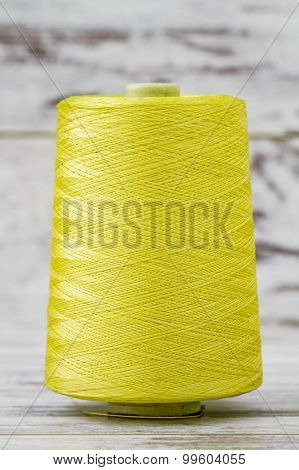 Spool Of Synthetic Green Thread On White Wooden Background