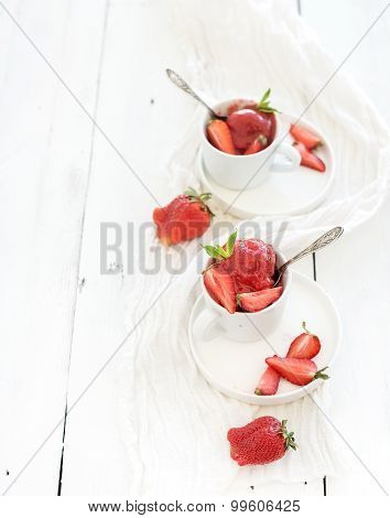 Strawberry sorbet ice-cream with mint leaves in cups over rustic white wooden background, top view