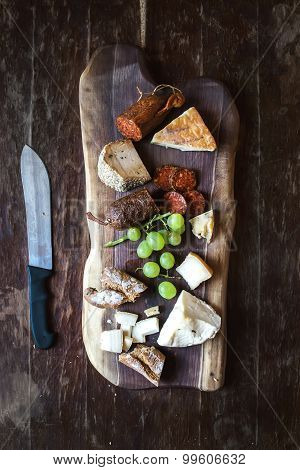Wine appetizers set: meat and cheese selection, grapes, bread on rustic wooden board over dark wood
