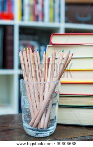 Colored Pencils With Pile Of Books In Background