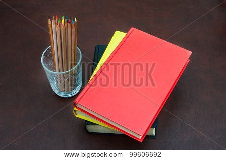 Colored Pencils And Pile Of Books On Wooden Desktop