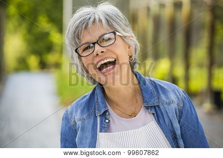 Beautiful mature woman working in a greenhouse, looking at camera while laughing