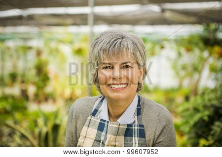 Beautiful mature woman gardening and looking at camera while smiling