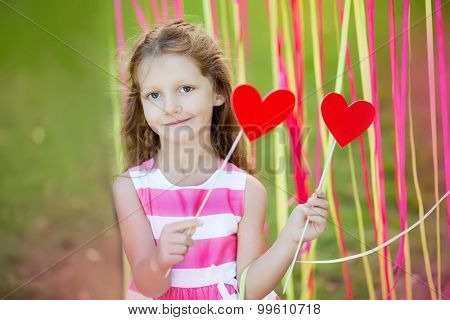 little girl in the festive decorations in the garden, holding hearts