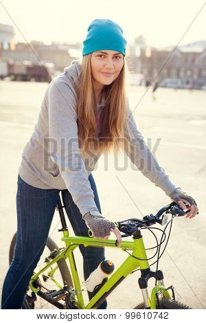 beautiful young woman with bike in the city