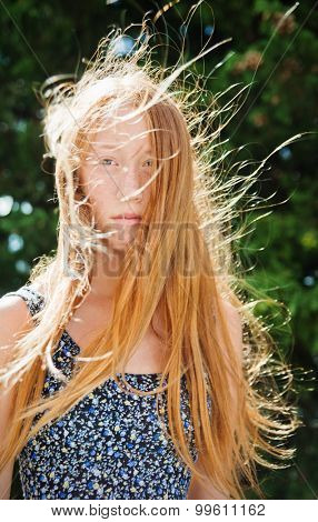 Portrait of young red haired girl on a windy summer day