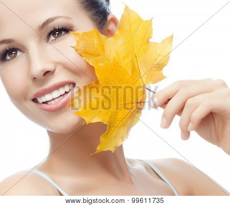 portrait of attractive  caucasian smiling woman isolated on white studio shot with yellow maple leaf