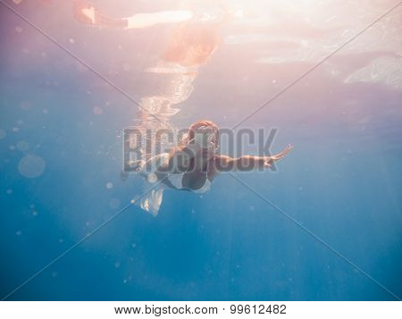Young woman swimming undewater in the swimming pool