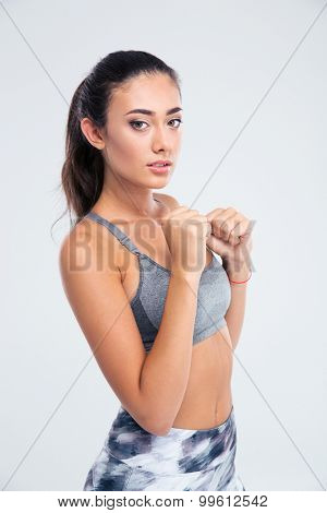 Portrait of attractive sports woman standing in defense stance isolated on a white background