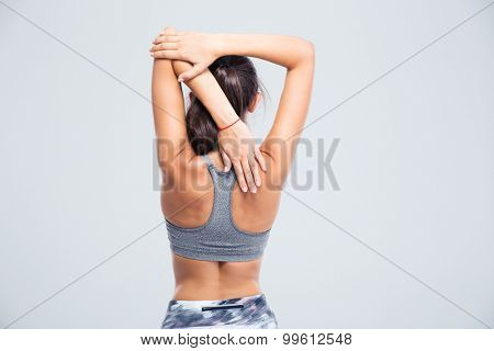 Back view portrait of a young woman stretching hands isolated on a white background