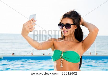 Portrait of a happy beautiful woman in bikini and sunglasses making selfie photo on smartphone outdoors