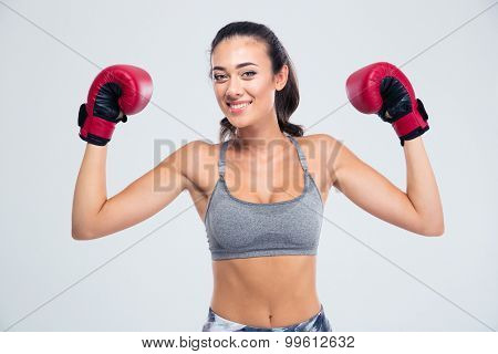 Portrait of a smiling fitness woman standing with boxing gloves in victory pose isolated on a white background