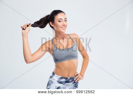 Portrait of a smiling sports woman holding her ponytail isolated on a white background and looking at camera