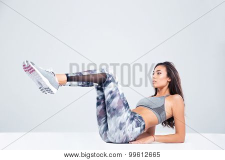 Portrait of a sports woman doing abs exercises isolated on a white background