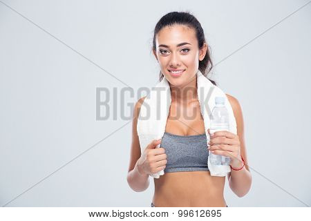 Portrait of a happy fitness woman with towel holding bottle with water isolated on a white background