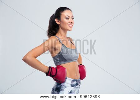 Portrait of a smiling sports woman standing in boxing gloves isolated on a white background