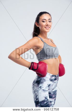 Portrait of a smiling fitness girl standing in boxing gloves isolated on a white background