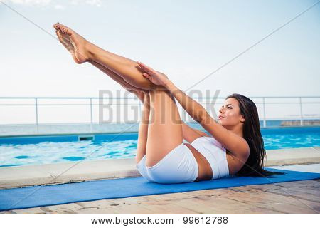 Portrait of a charming woman stretching on yoga mat outdoors in the morning