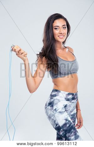 Portrait of a smiling sports woman holding skipping rope isolated on a white background
