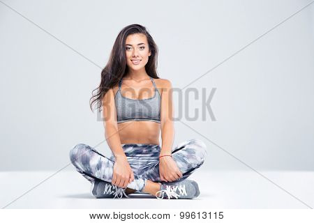 Portrait of a smiling fitness woman sitting on the floor isolated on a white background