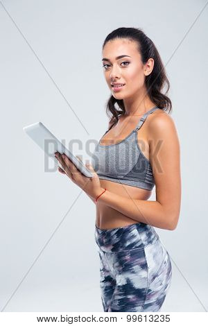 Portrait of a happy sporty woman using tablet computer isolated on a white background and looking at camera