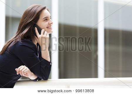 Cute business woman talking on the phone at modern office building