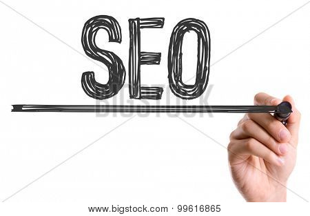 Hand with marker writing the word SEO