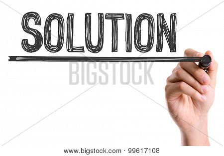 Hand with marker writing the word Solution