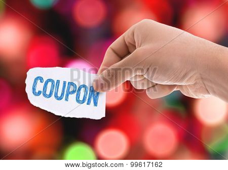 Piece of paper with the word Coupon with bokeh background