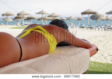 Suntanned Woman Lying On Massage Table