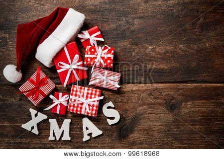Christmas Santa Claus hat with gift boxes and decoration over grunge wooden background