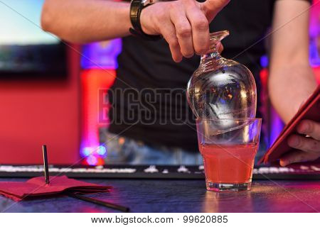 Closeup photo in a bar where barmen makes cocktail