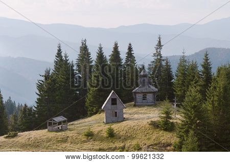 Mountain landscape with an old wooden church in the spruce forest. Carpathians. Ukraine. Europe