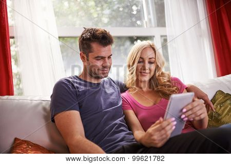 lovely couple sitting on couch at home watching videos on tablet together