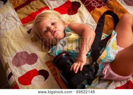 Little Blonde Girl Lies On Sofa Examines Photo Camera