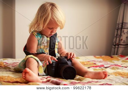 Little Blonde Girl Tries To Put On Camera Against White Wall