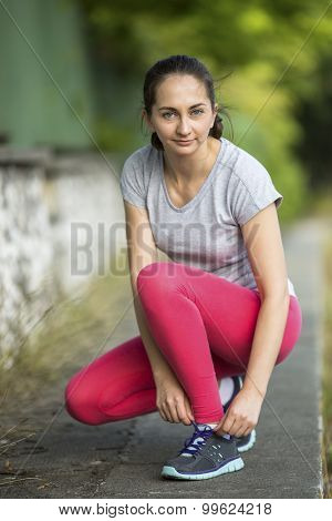 Young sporty woman tying running shoe laces before Jogging in park in sunshine on beautiful summer day. Sport fitness model caucasian ethnicity training outdoors. Workout in a Park.