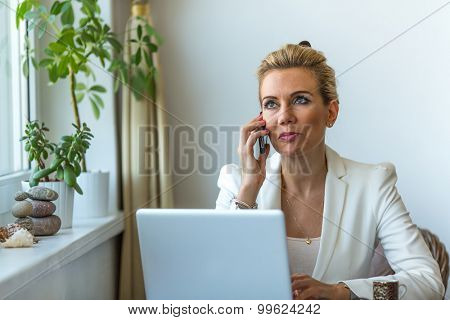 Attractive business woman working on laptop computer and speaks mobile phone. Conversation with the client. Successful business woman speaks on a cell phone.