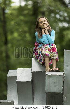 Cute little cute girl sitting in the Park.