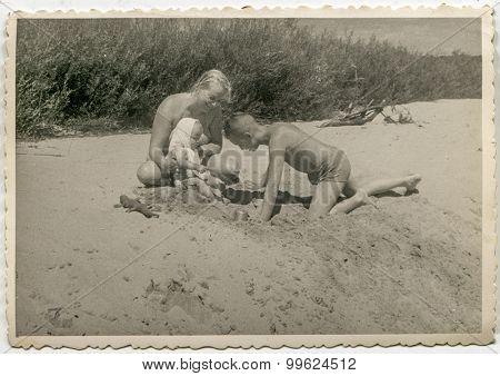 Vintage photo of mother playing on beach with her son and baby daughter, 1955