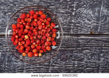 Fresh wild strawberry on the clear glass plate over wooden background