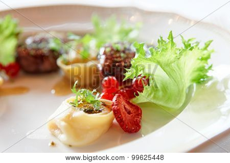 Duck meat with berries and ravioli, close-up, gourmet food