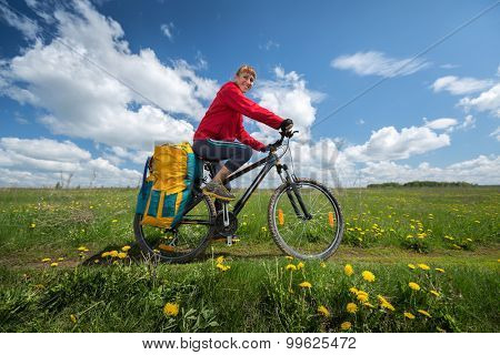 Smiling lady with loaded bicycle standing on a green meadow with flowers