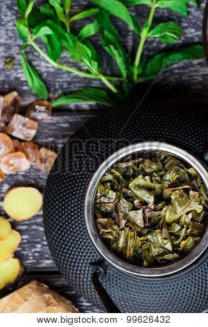 Black iron asian tea set with green tea leaves, closeup view